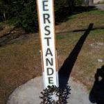 """Detailaufnahme des Holzkreuzes mit der Aufschrift """"Der HERR ist Auferstanden. Er is wahrhaftig Auferstanden."""" am Ostermorgen vor der St. Andreas Kirche"""