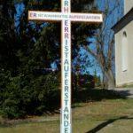 """Neu errichtetes Holzkreuz an der Kirche St. Andreas mit dem Ostergruß """"Der HERR ist auferstanden, er ist wahrhaftig auferstanden."""""""